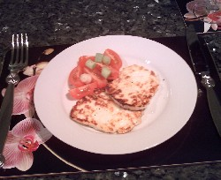 Serving griddled Halloumi cheese with tomato and spring onion